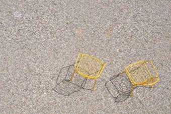 Zwei gelbe Stühle stehen auf grauem Untergrund. Die Stühle sind leer.